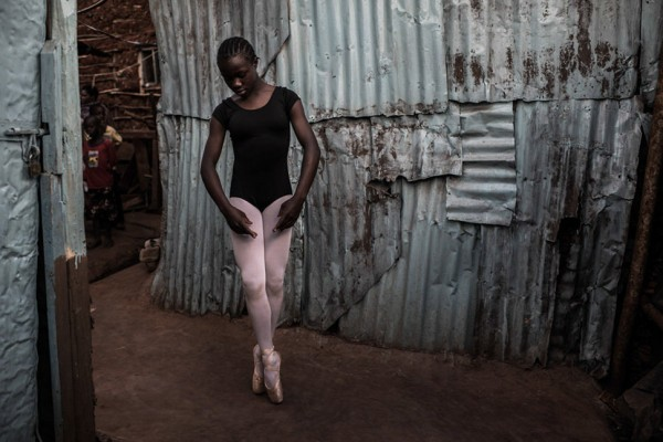 Pamela is practicing Ballet outside her family's house in Kibera.